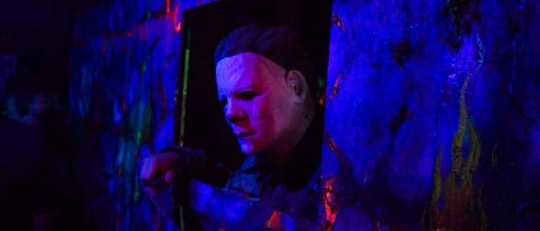 Michael Myers peering through a window at a haunted house.
