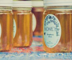 Jars of honey on a farmers market table.