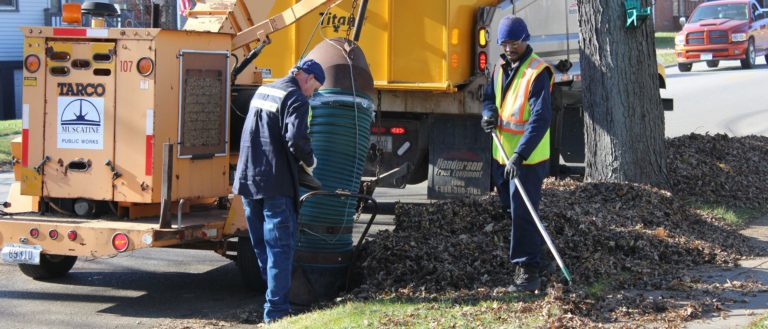 A city crew picking up leaf collection on the sidewalk.