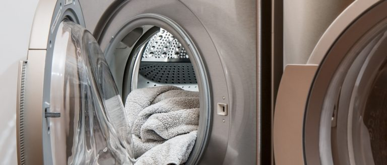 A dryer with towels hanging out of it.
