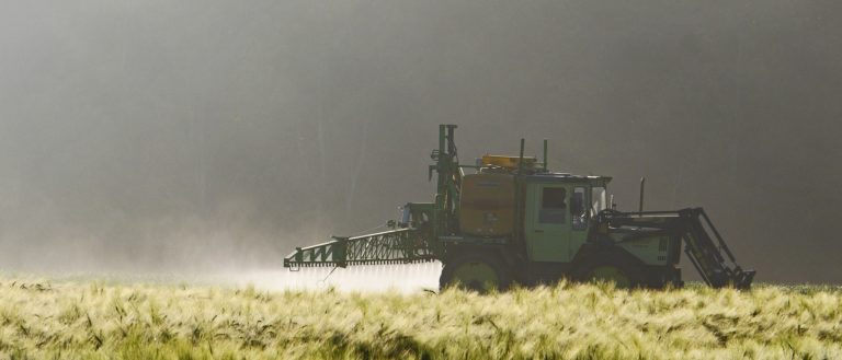 A tractor spraying pesticide on crops.