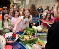 Students in a cafeteria looking at healthy food items.