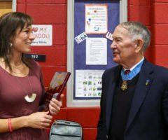 A teacher receiving an award from a Medal of Honor recipient.