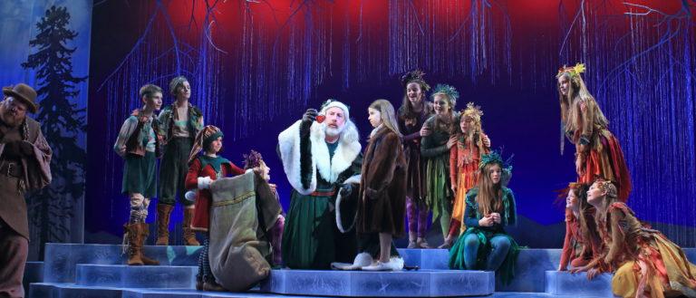 Children surrounding a grey-bearded elder on stage.