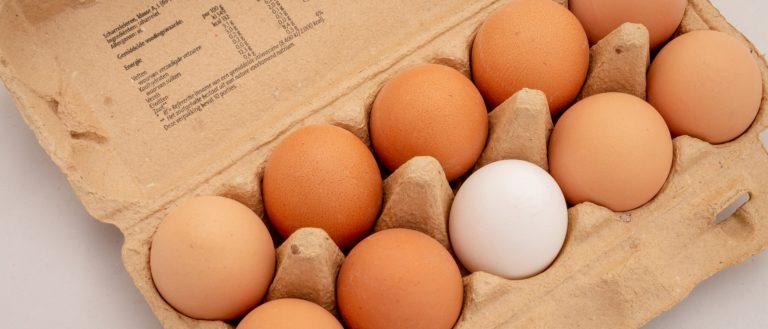 A carton of eggs on a table.