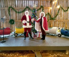 Santa Claus and Mrs. Claus in a barn.