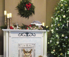 A Christmas tree and decorations near a fireplace.