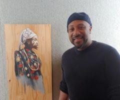 An artist standing next to a portrait.