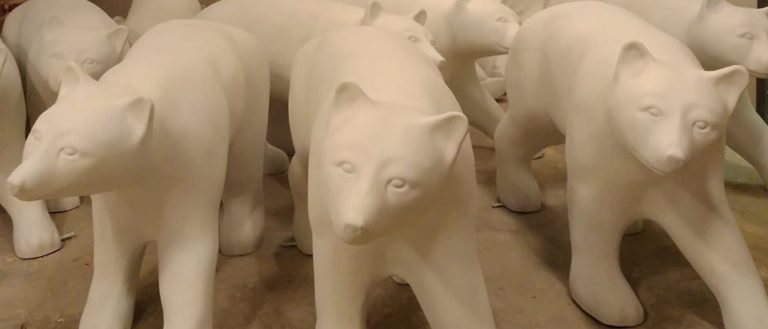 Unpainted bear sculptures in a room.