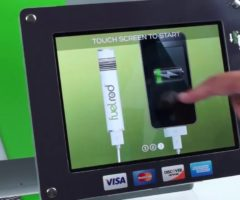 A hand touching a FuelRod station's display.