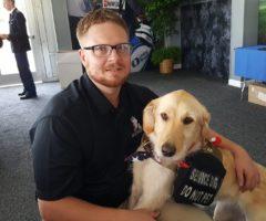 A man sitting next to a service dog.