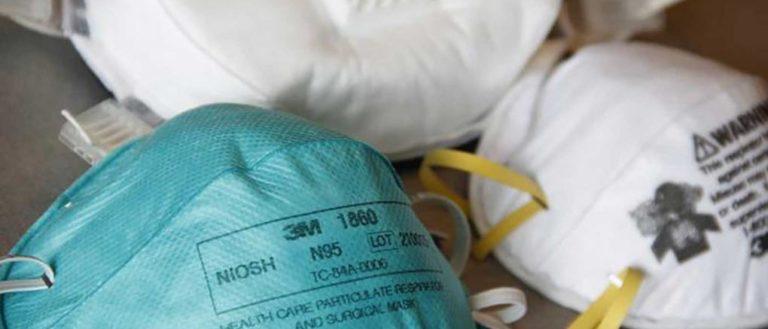 Three N95 respirator masks on a table.