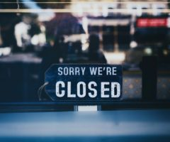 A closed sign on the entrance of a store.