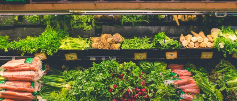 A shelf of vegetables at a grocery store.