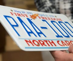 A person holding a North Carolina license plate.