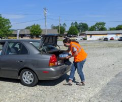 A person loading pet foot into the trunk of a car.