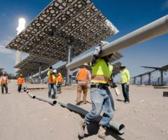 Contractors work to install pipe at a solar thermal facility.