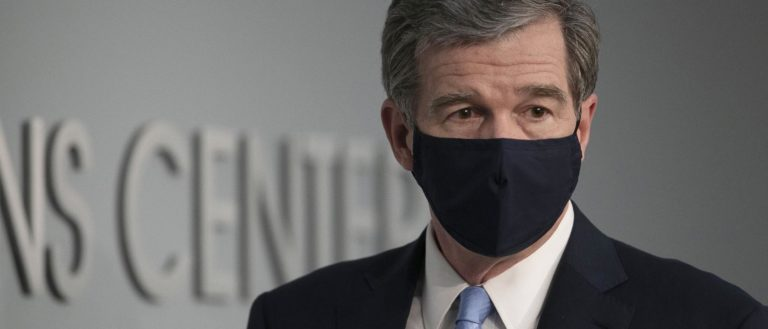 A man in a suit wearing a black mask.