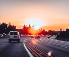 Cars driving on the interstate under a sunset.