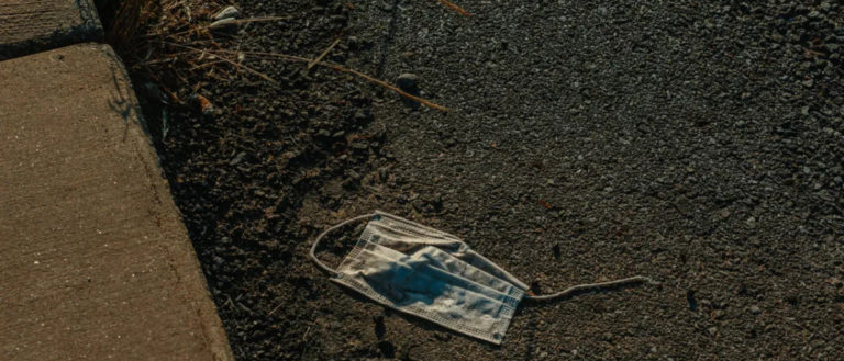 A discarded surgical mask on the ground.
