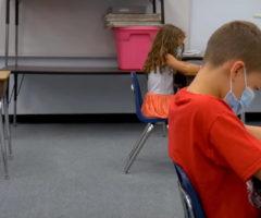 A classroom of children at desks spaced far apart.