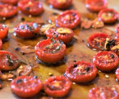 Sliced tomatoes on an oven sheet.