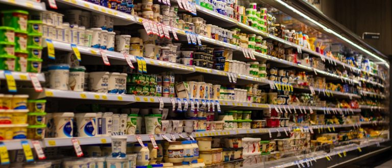 Refrigerated dairy items in a grocery store aisle.