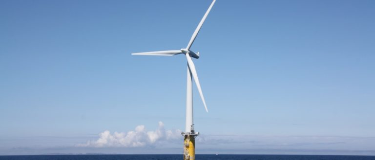 An offshore wind turbine floating on a yellow foundation.