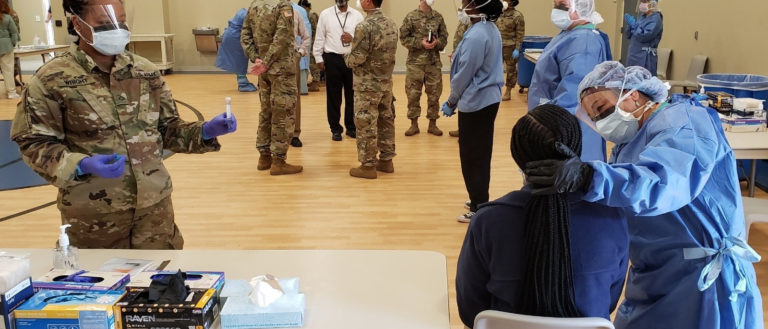 Health care workers and soldiers vaccinating people in a gym.