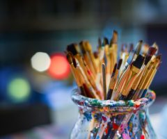 Paint brushes in a vase on top of art supplies.