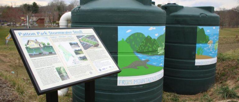 Big green water barrels next to signage.
