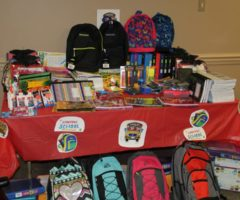 A table full of donated school supplies.