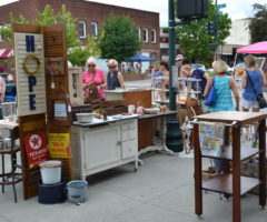 People on a street exploring arts and craft vendor booths.