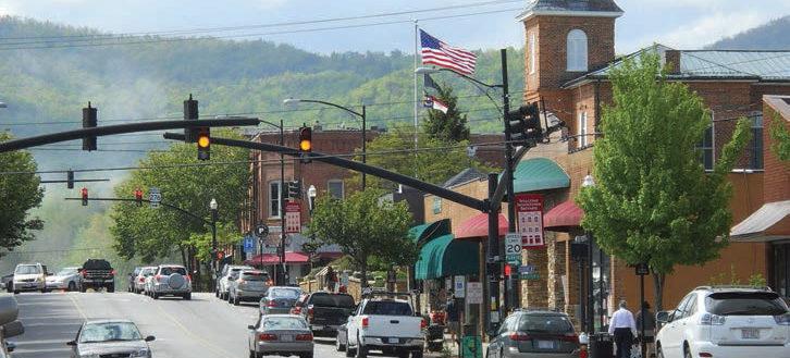 Cars driving through a Main Street of a town.