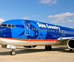A blue and orange airplane on tarmac.