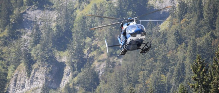 A helicopter flying through a mountain range.