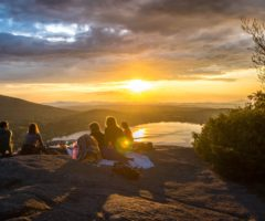 A group of hikers having a picnic on top of a mountain at sunset.