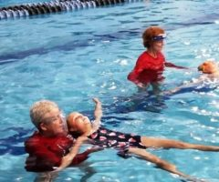 Two children learning how to swim in a pool.