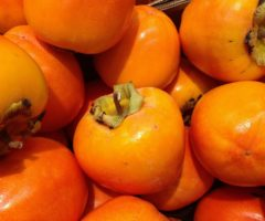 Several persimmons on top of one another.