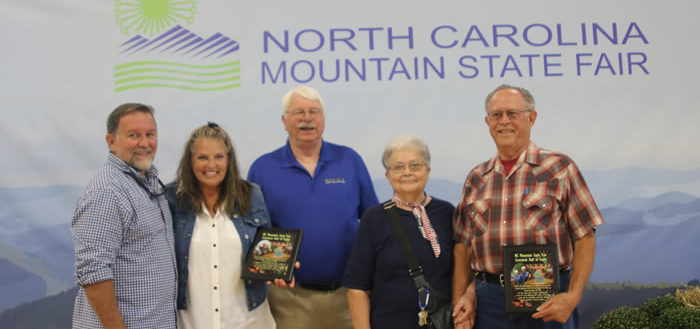 Five people standing in front of a Mountain State Fair sign.