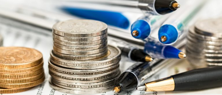 Money, coins, and pens on top of tax papers.