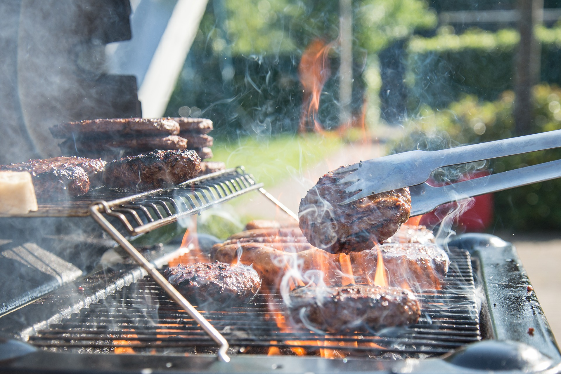 A person barbecuing hamburgers and hot dogs on the grill.