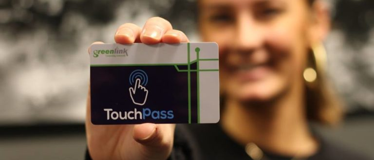 A Greenlink worker holding up a TouchPass.