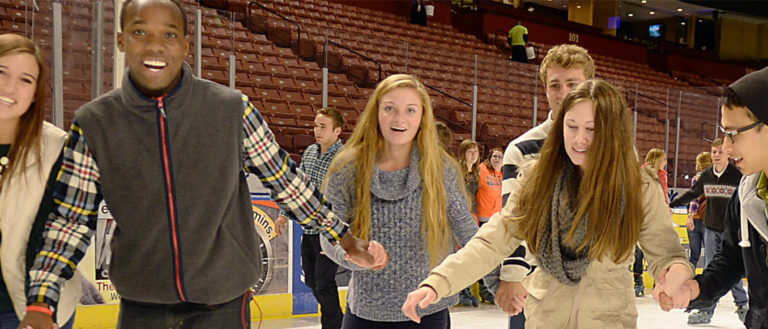 Teenagers skating on an ice rink while holding hands.