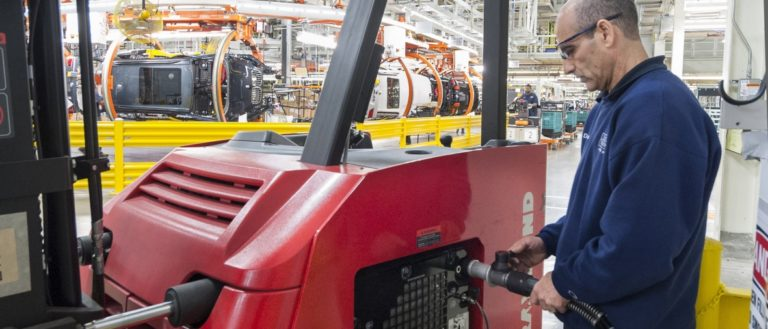 A BMW Spartanburg worker filling a fuel cell fork lift with power.