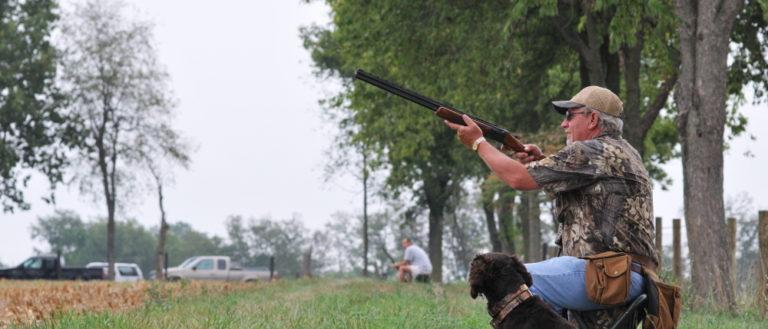 A dove hunter aiming his gun to the sky.