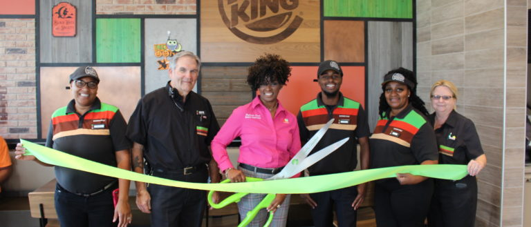 Burger King employees cutting the grand opening ribbon at their east Greenville location.