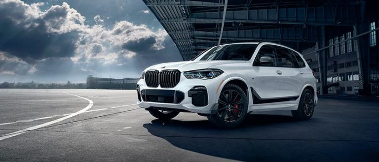 The BMW X5 2019 under a bridge on a cloudy day.