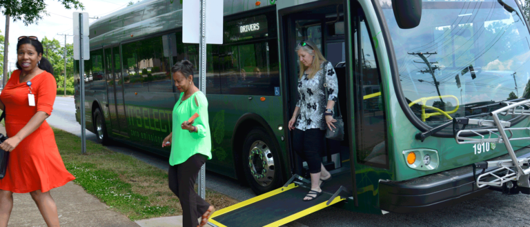 People exiting a Greenlink bus at a bus stop.