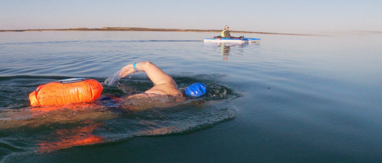 Melinda Menzer swimming with a float.